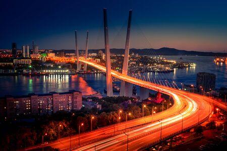 Cityscape overlooking the Golden bridge in blue hour. Bright illumination adorns the night city. Vladivostok, Russia 写真素材 - 129113825