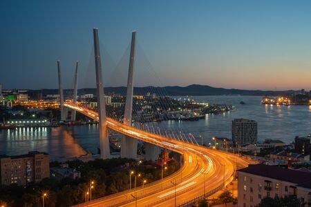 Cityscape overlooking the Golden bridge in blue hour. Bright illumination adorns the night city. Vladivostok, Russia 写真素材 - 129113826