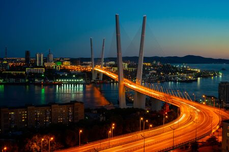 Cityscape overlooking the Golden bridge in blue hour. Bright illumination adorns the night city. Vladivostok, Russia 写真素材 - 129113830