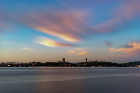 Seascape overlooking the city on the horizon. Charged with long videjko. Beautiful sunset in soft pastel colors. Vladivostok, Russia