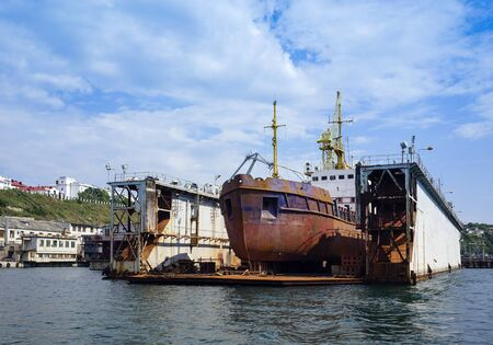Landscape with a floating dock and a rusty ship inside. Sevastopol, Crimea 写真素材