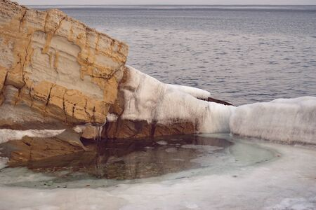 Sea landscape with the yellow rock and ice floes