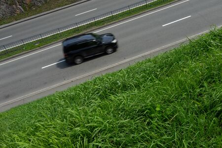 Background with road and car, roadsides overgrown with green grass. 写真素材