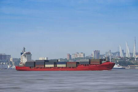 Seascape with a red container ship on the background of the cityscape. Vladivostok, Russia 写真素材 - 133128993