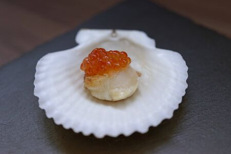 Red caviar on a scallop fillet and on a white shell on a dark slate background. 写真素材 - 133345321