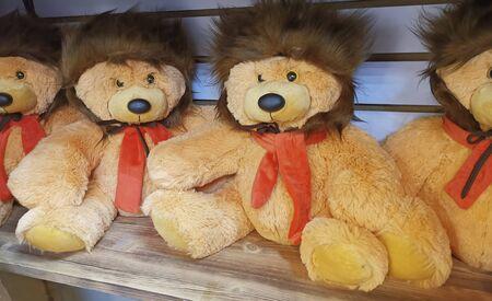 Teddy bears in fur hats on wooden shelves Zdjęcie Seryjne