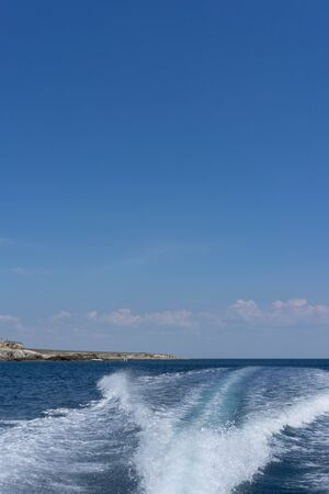 White foam trail from the movement of the boat on a blue background. Travel by sea.