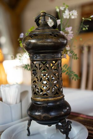 Beautiful metal lamp with ornament on a blurred background