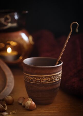 Dark background with a hot drink in a ceramic Cup and the scattered nuts hazelnuts on a wooden surface. 写真素材