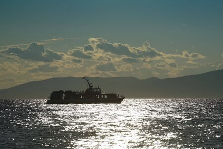 Silhouette of the ship against the seascape in the contra light