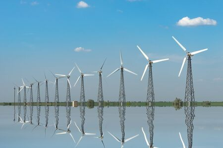 Natural landscape with windmills reflected in the water.