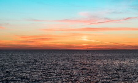 Sunset over the sea surface. Beautiful sky above the horizon.