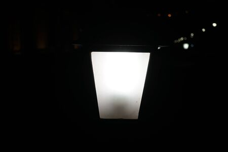 Black background with a glowing white lantern in the middle.