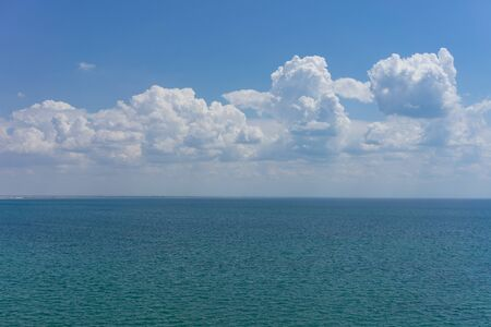 Seascape with water surface and sky with clouds.
