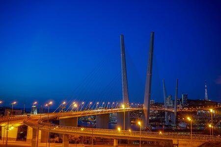 Golden bridge against the blue evening sky. Vladivostok, Russia