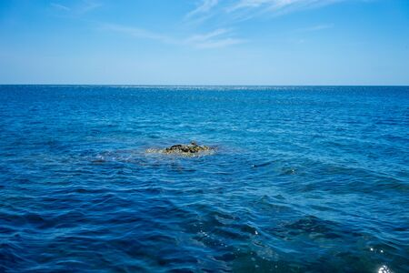 Seascape with a small rock on the background of water. 写真素材