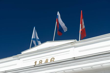 Sevasopol, Crimea. Flags on top of a white colonnade against a blue sky.