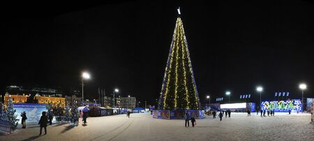 Vladivostok, Russia-January 13, 2020: Panorama of the city landscape at night. A Christmas tree adorns the Central square, people are resting among the illumination.