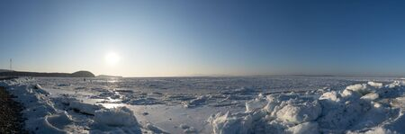 Panorama of the frozen Amur Bay with snow and ice floes. Vladivostok, Russia Standard-Bild