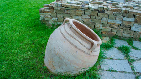 Taman, Krasnodar territory.Clay pot on a background of stones and grass.