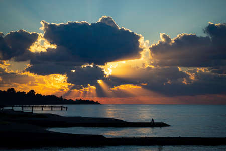 Seascape with a bright sunset and rays through the clouds.