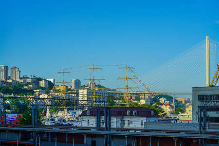 Vladivostok, Russia-June 12, 2020: Industrial landscape with a view of the masts of a sailboat and the Golden bridge against the sky.