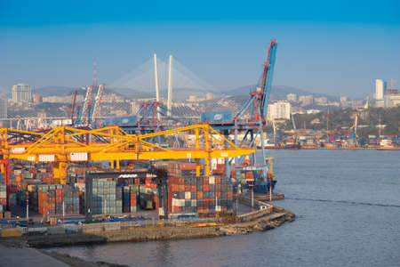 Vladivostok, Russia-September 29, 2019: Landscape with views of the commercial port, containers, cranes and ships. In the background, the citys landmark is the Golden bridge.