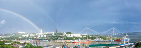 Panorama of the city landscape with a view of the Russian bridge and the rainbow in the sky. Vladivostok, Russia 写真素材
