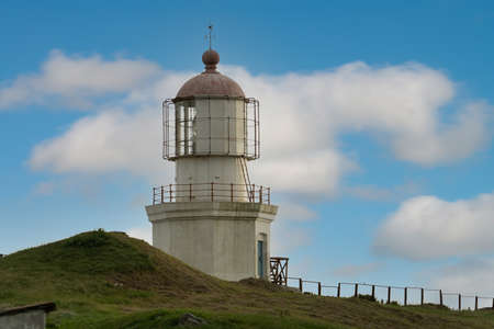 Vintage the lighthouse at Cape Pospelova on the background of blue sky. Nakhodka, russia Reklamní fotografie