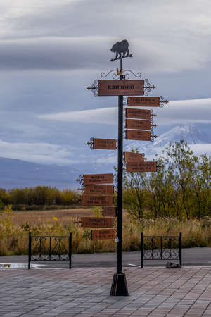 A pole with a direction indicator on the background of volcanoes in Kamchatka. Travel to Russia