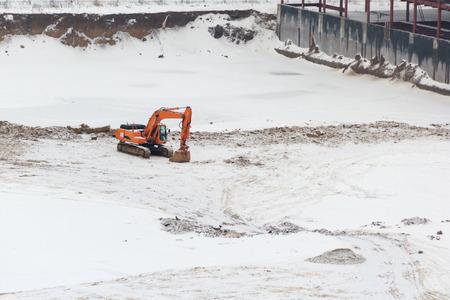 digging: orange excavator digging with snow