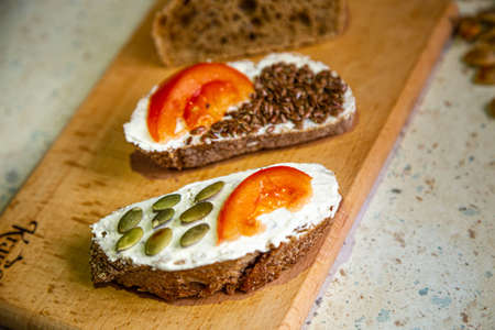 fast cooking food at home, eco bread with cream cheese, tomato slices, pumpkin and flax seeds, close up on the table, vegan snack