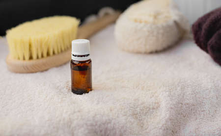 the essential oil in an amber glass bottle, white towel, body brush, copy space, spa procedures products, eco cosmetic,