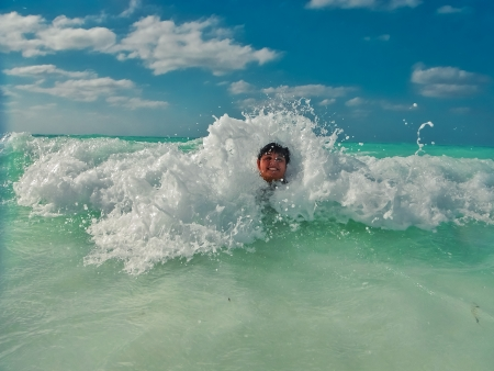 boy swimming in ocean waves photo