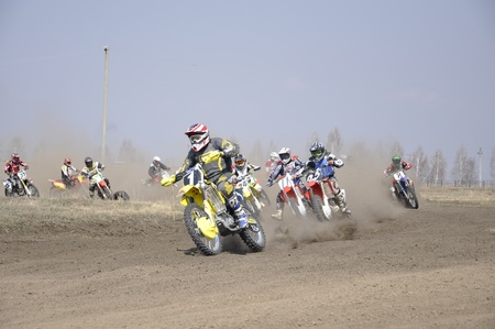 Russia, Samara - April 17,2010, Regional Championship motocross, a group of riders the first corner after the start, the dusty trail