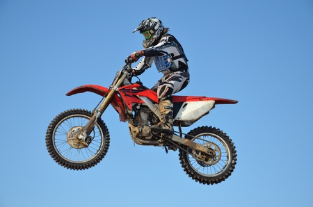 Motocross, rider A. Stepanov performs jump, located high in air against blue sky