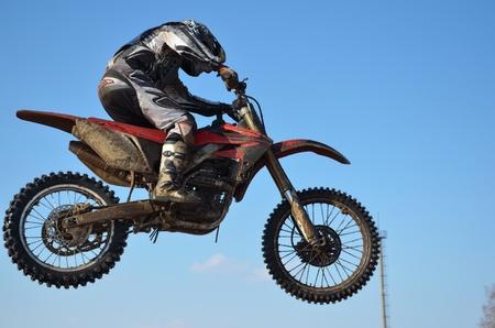 super cross: Piloto de motocross A. Stepanov realiza salto, situado en alto en el aire contra el cielo azul