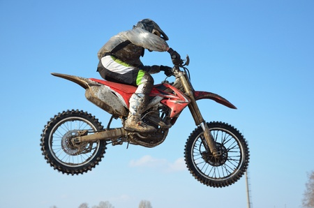 Motocross rider O. Safiullin performs jump, located high in air against blue sky Stock Photo - 9138539