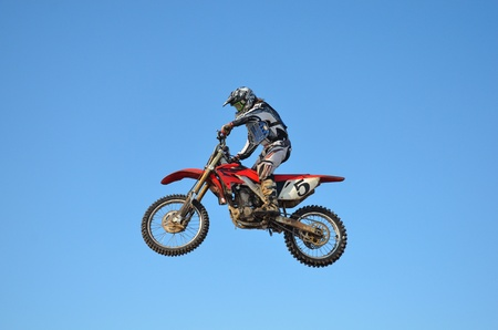 Motocross rider performs jump, located high in air against blue sky Stock Photo