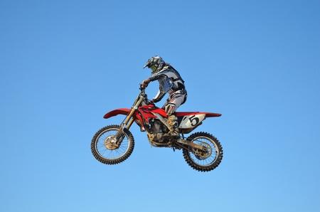 super cross: Piloto de motocross realiza salto, situado en alto en el aire contra el cielo azul