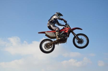 super cross: Motocross, jinete realiza salto, situado en alto en el aire contra el cielo azul