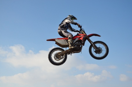 Motocross, rider performs jump, located high in air against blue sky