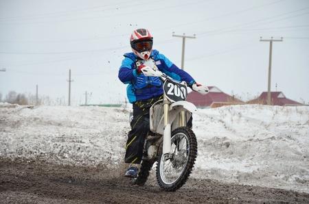 super cross: Hojas de piloto de motocross gire con derrape en el camino fangoso, cubierto de nieve