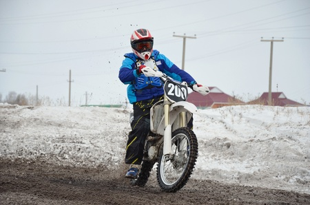 skidding: Motocross rider leaves turn with skidding on the muddy, snowy road