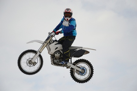 Motocross rider performs a high jump looks toward