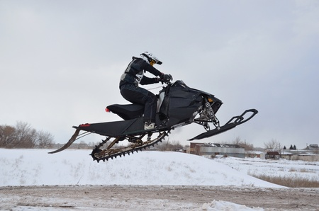 rider on the snowmobile jumping is outdoors