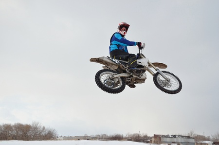 motocross practice rider high flight with the slope of the motorcycle and turning the head, look back photo