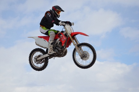 super cross: Jinete de pr�ctica de motocross realiza un salto eficaz, situado en alto en el aire contra el cielo azul