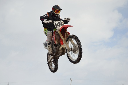 motocross rider performs jump, located high in the air Stock Photo - 9138599