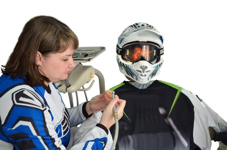 Woman dentist in the hands of dental prostheses in the form at the dental chair is casual shirt and a motorcycle helmet on a clean background